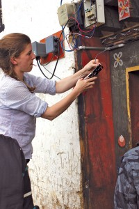 Meg installs a GridShare device in Rukubji. (Photo credit Arne Jacobson.)