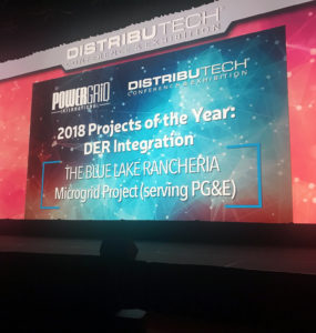 A presenter stands against the award screen at the DistribuTECH conference.