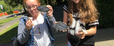 Two middle school students hold solar modules and fans in the sun.