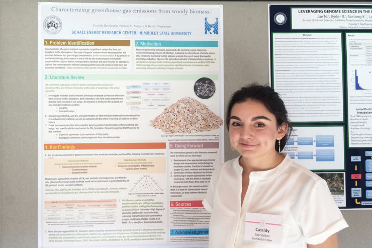 Cassidy Barrientos stands in front of the project poster, wearing a white blouse and a nametag
