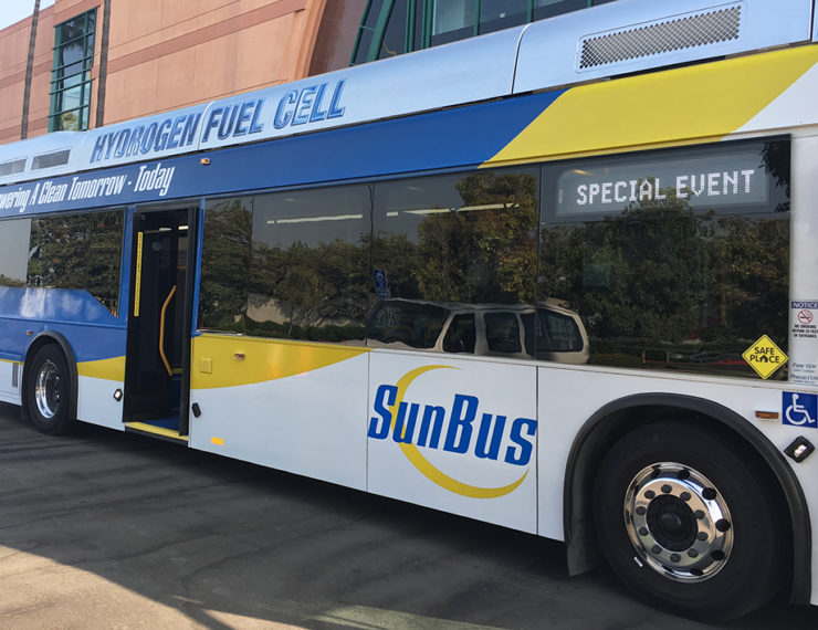 "A hydrogen fuel cell ""SunBus"" sits outside a conference center."