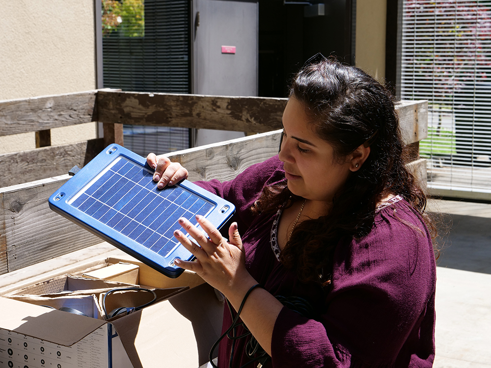 Tanya Garcia unpacks a solar module in the Schatz courtyard.