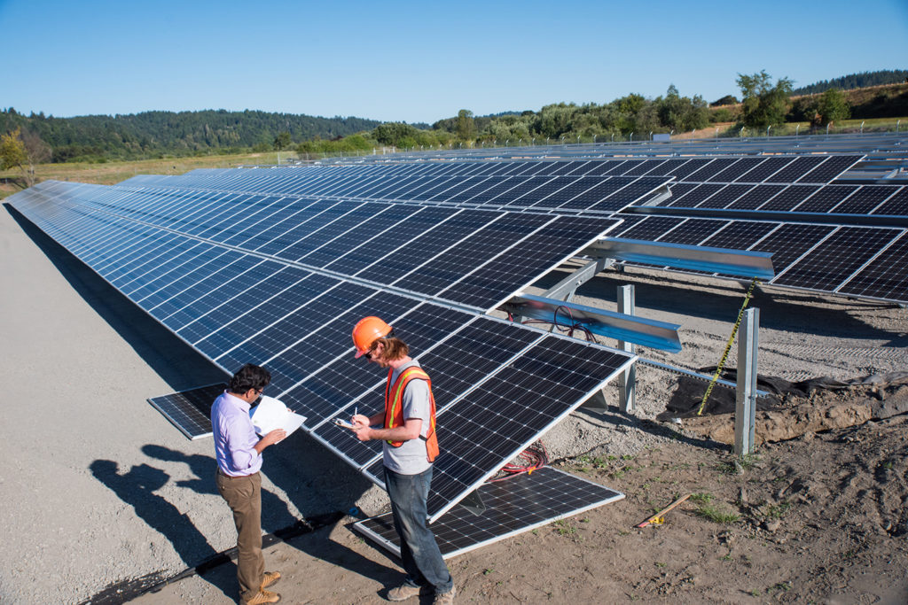 Two students refer to a blueprint at the Blue Lake Rancheria solar array.