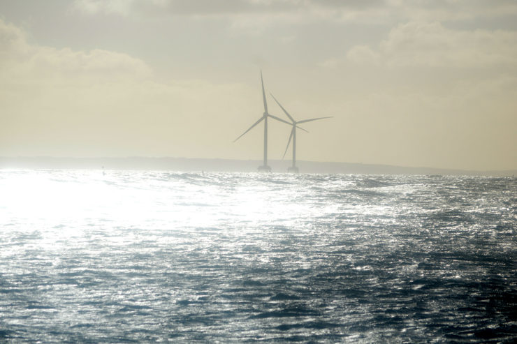 Light shines brightly over two offshore wind turbines and the ocean
