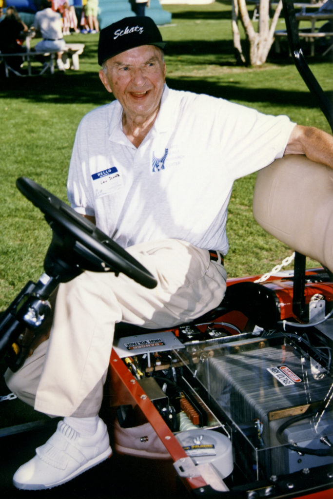 Louis Schatz, wearing a Schatz Center cap and shirt, sits on a fuel cell vehicle with the fuel cell shown.