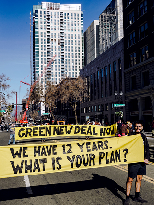 "Protesters hold banner signs that stretch across a city road: ""GREEN NEW DEAL NOW"" and ""WE HAVE 12 YEARS. WHAT IS YOUR PLAN?"""
