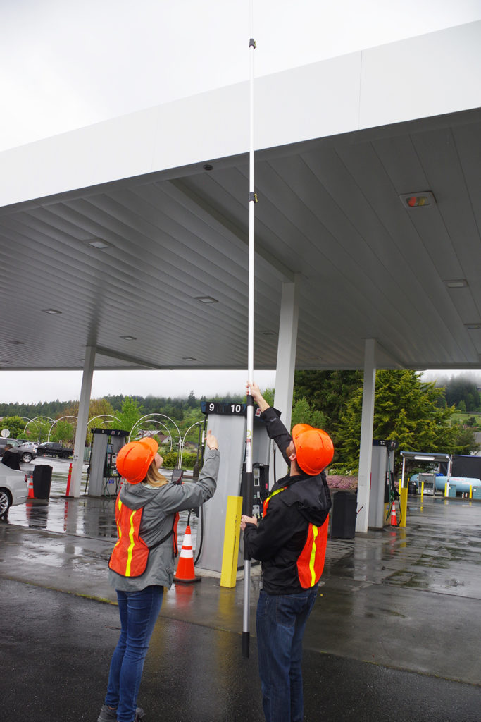 Two students use a GoPro on an extension pole to take canopy measurements at a fueling station