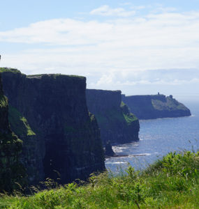 On a sunny day, steep, green-topped cliffs form a wave pattern against blue ocean