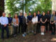11 students stand together beneath redwoods