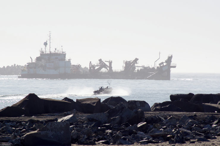 A dredge ship and small fishing boat in the mouth of Humboldt Bay)