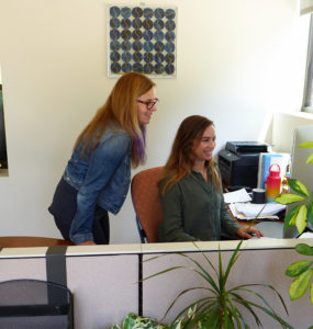 Two staff work at a computer