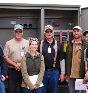 4 Schatz engineers and 2 electricians stand outside an open energy storage cabinet