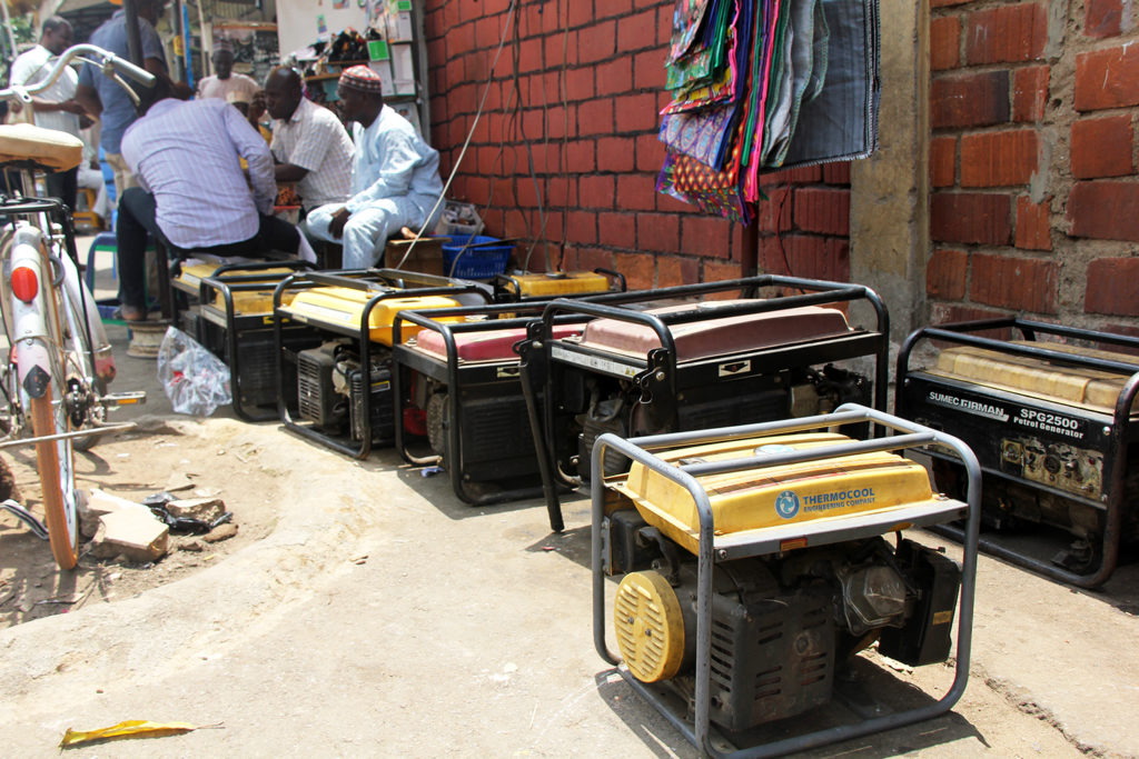 Men sit near an array of generators