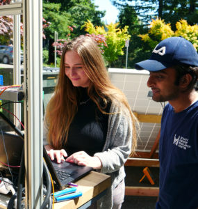 Two people measure the efficiency of a solar water pump