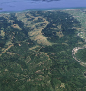 Aerial shot of mountains, with Highway 101 and the town of Scotia to the left, and the Pacific Ocean to the north