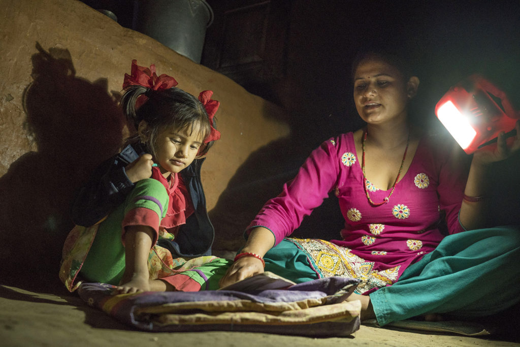 Ambika Parajuli holds a solar lamp to help her four year old daughter do homework.