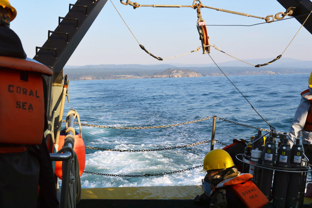 Two researchers sit near the stern with the shore receding in the distance
