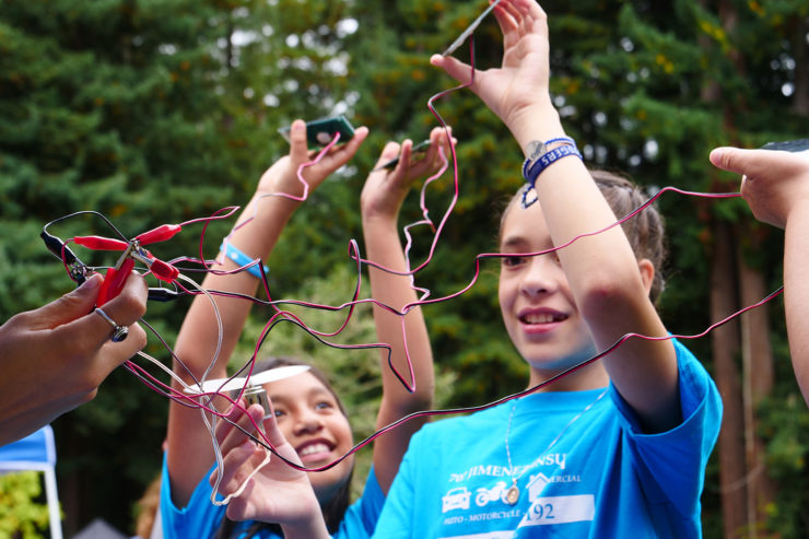 Volunteers and youth hold solar panel circuits toward the sun
