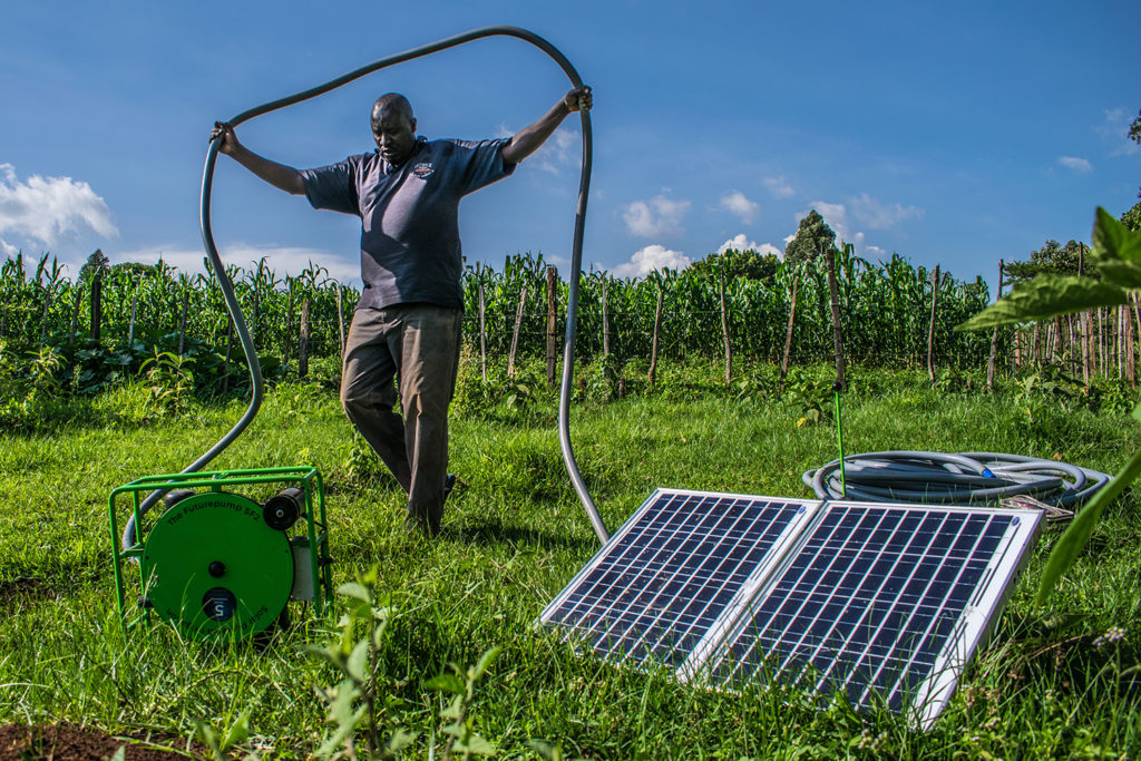 A man stands in a lush green farm, unspooling a hose next to a solar module.