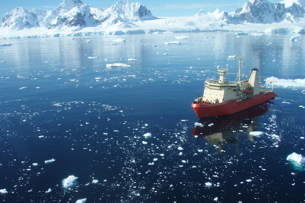 A research vessel crosses through blue water with sporadic floating ice. An icy shore and peaks are behind. The ship is orange at the base and white in the upper decks.