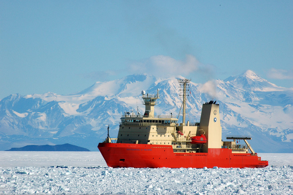 A vessel moves through icy waters with snow covered mountains behind. The ship is orange at the base, and offwhite in the upper decks.