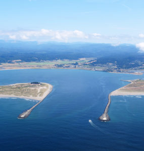 An aerial view of the entrance to Humboldt Bay, where a small boat enters between two jetties.