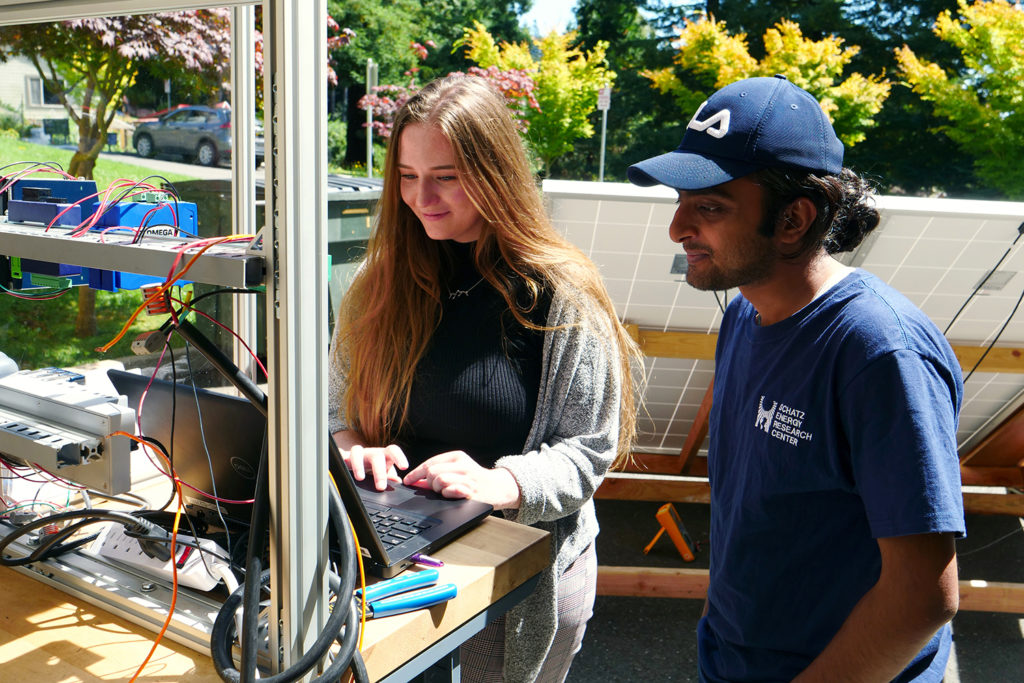 Two students work outdoors at a test station