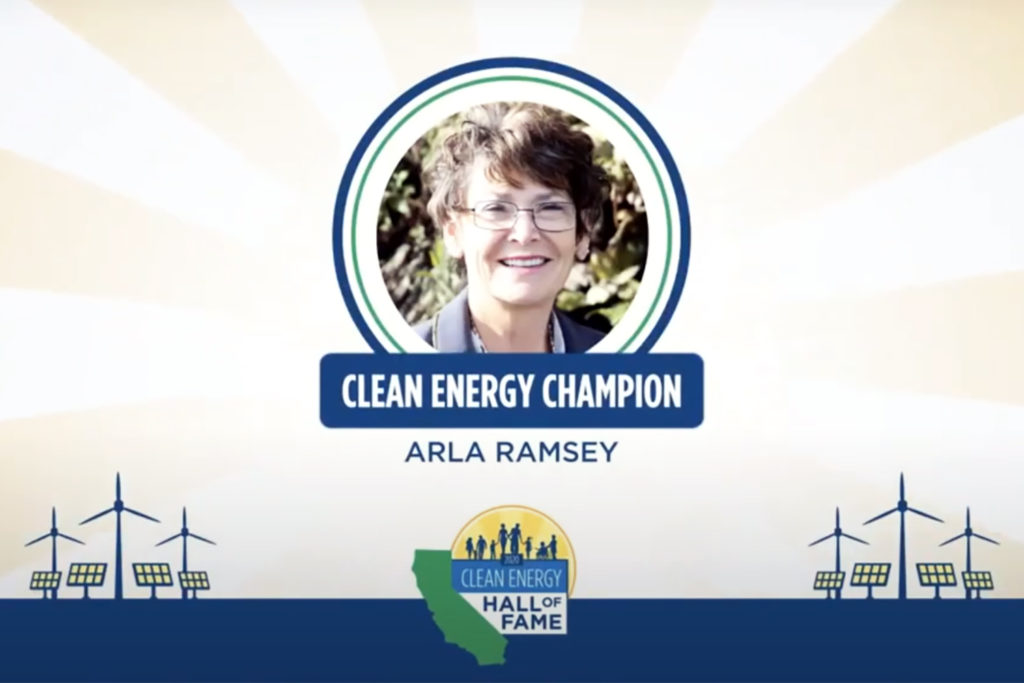 """A smiling woman with the caption """"Clean Energy Champion: Arla Ramsey"""" beneath her photo."""