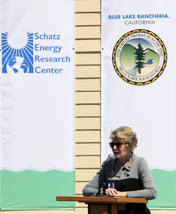 A woman standing in full sun speaks into a podium microphone, with logo banners for the Schatz Energy Research Center and the Blue Lake Rancheria hanging on the wall behind her.