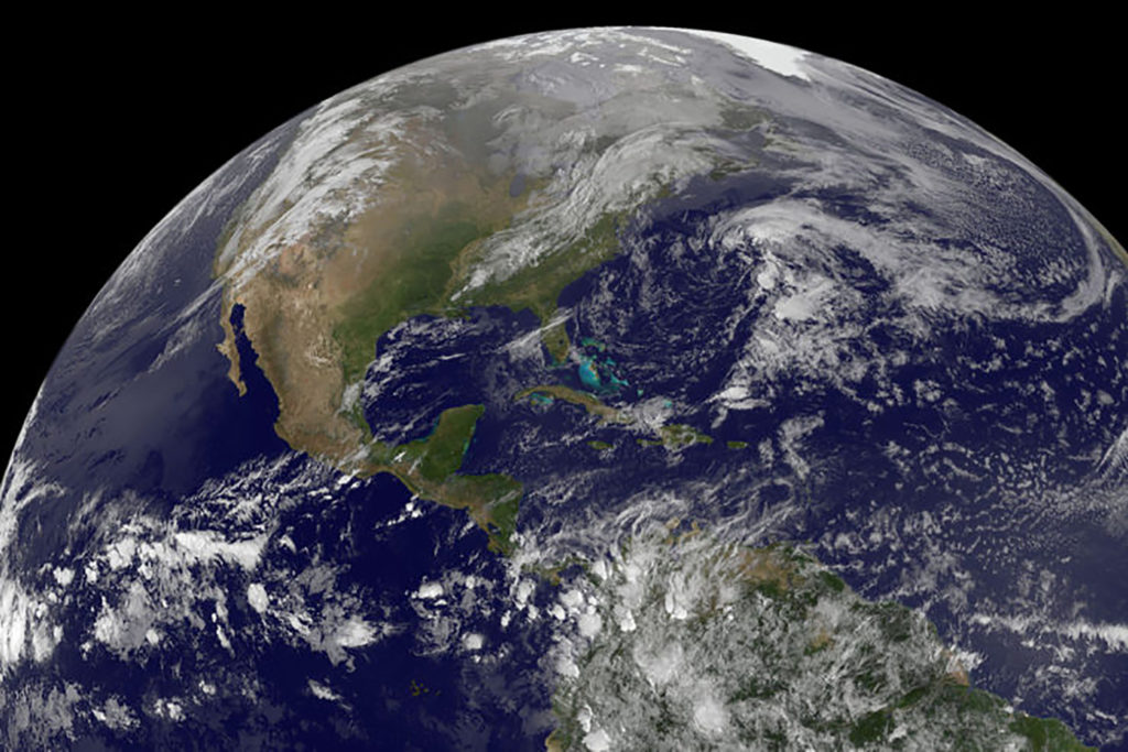 A satellite image of the earth shows North and Central America and surrounding oceans, while the upper part of South America is lightly covered by clouds.