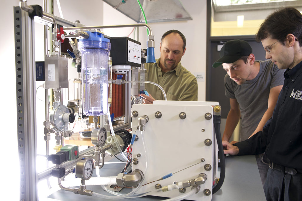 Three engineers look closely at a hydrogen fuel cell stack