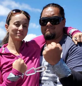 Two people stand with one arm around each other's shoulder and the other wrists locked together