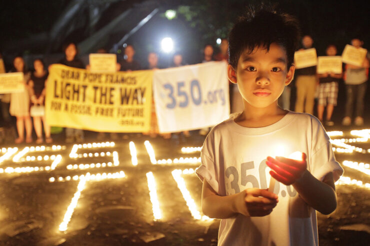 """A child is holding a candle and wearing a shirt that says """"350.org"""""""