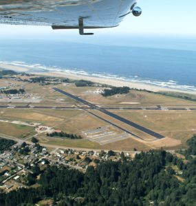 The aiport landing strips and ocean are shown beneath a plane's wing.
