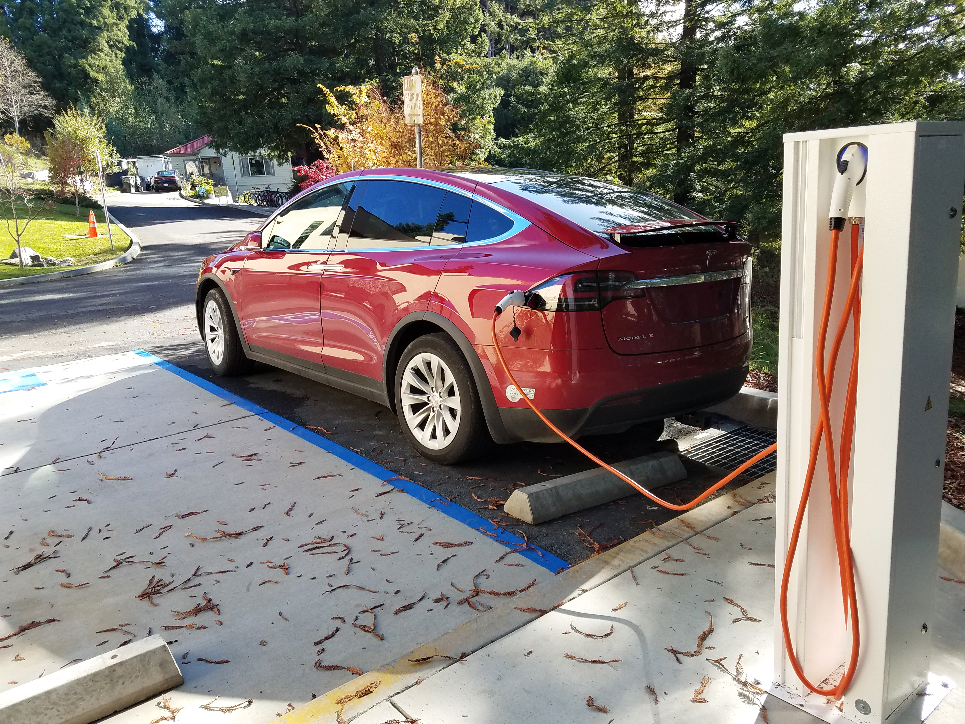 A red Tesla is charging at the Schatz EV station.