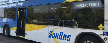 """A hydrogen fuel cell """"SunBus"""" sits outside a conference center."""