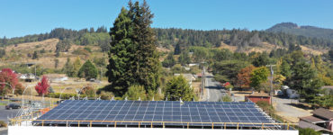 """Overhead shot shows solar modules on the canopy of the fueling station"