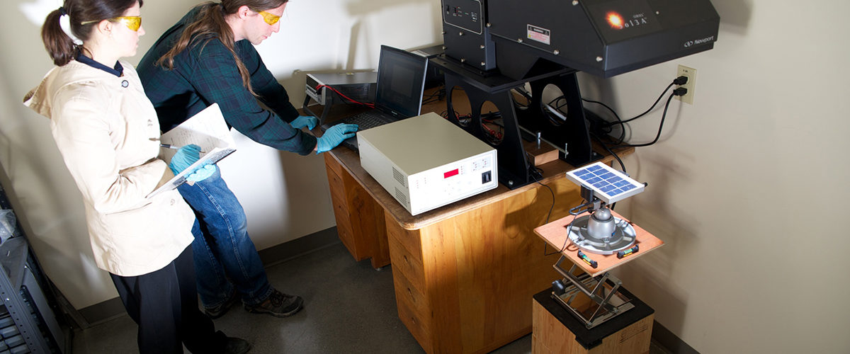 Two engineers use a solar simulator to test a solar module
