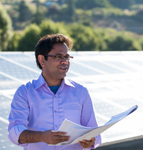 A graduate student engineer holds blueprints while standing next to a solar array