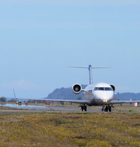 A plane moves along the runway, with Trinidad, CA in the distance