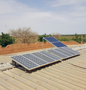 A clinic worker stands on the roof beside a small solar array