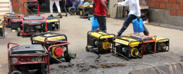 Men walk past an array of generators which are leaking fuel