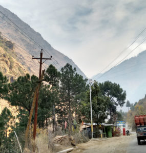 A truck drives past a small roadway shop in the mountains, with power lines overhead.