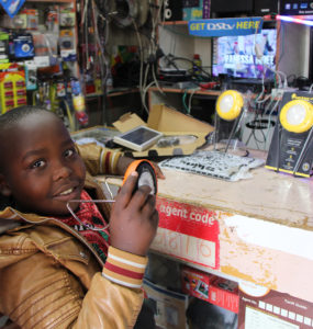A child holds a solar product while standing at a store counter