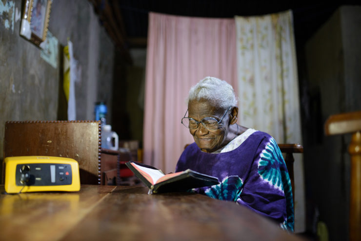 A elder woman reads at a dining room table by solar light