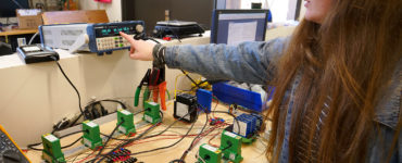 A woman points at output from a testboard