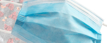 A blue surgical mask is superimposed over a graphic of a coronavirus