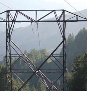 A closeup of a transmission tower between tree-covered hills