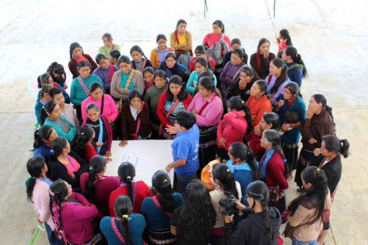 Over 50 women gather in a close circle to listen to a speaker