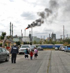 A family walks along a residential street, at the end of which is a refinery with a smoky plume